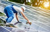 Construction worker connecting photo voltaic panel to solar system using screwdriver on shiny surface and lit by sun green tree background. Alternative energy and financial investment concept. poster
