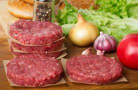 Various Raw Burger Ingredients On Wooden Desk