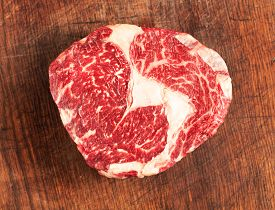 Top View Of Raw Rib-eye Steak On Wooden Background
