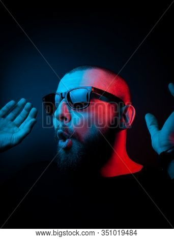Studio Portrait Of A Charismatic Guy In Neon Style. Stock Photo Of A Bearded Guy Surprised By Surpri