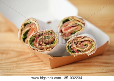 Cream Cheese Salmon Tortilla  Roll-ups in a takeaway box