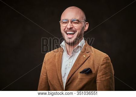 Successfull Well-dressed Bald Smiling And Laughing Businessman Posing For Camera In A Dark Studio We