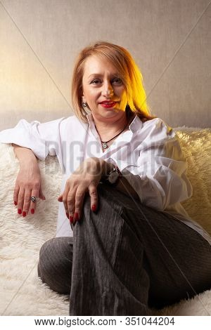 Portrait Of An Attractive Middle-aged Woman. Homemade Portrait On The Couch, Middle-aged Blonde.