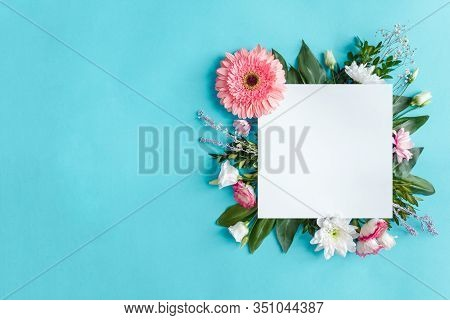 Blank Square Sheet Of Paper On Blue Background. Composition Of Pink And White Flowers Are Lined With