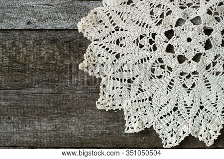 Handmade Crocheted Napkin Made Of Fine Cotton Yarn. Crocheted Napkin Lies On An Old Wooden Backgroun