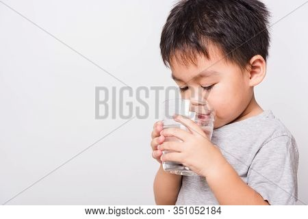 Closeup Asian Face, Little Children Boy Drinking Water From Glass On White Background With Copy Spac