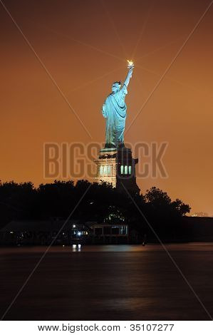 Statue of Liberty at night lit by lights in Liberty Park in New York City.