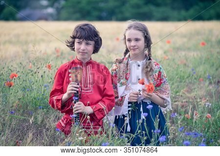 Portrait Of A Boy And A Girl In The Field. The Shoulders Of Girl  Are Covered With A Shawl With Russ