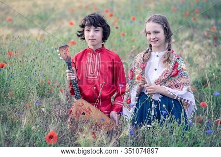 Portrait Of A Boy And A Girl In The Field. The Shoulders Of Girl Are Covered With A Shawl With Russi