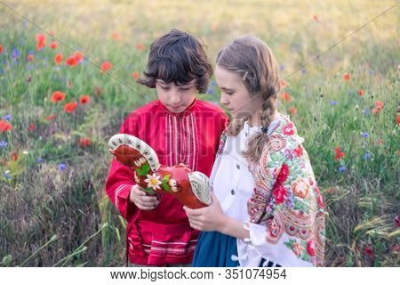 Portrait Of A Boy And A Girl In The Field. On The Girl Is A Shawl With Folk Patterns. Boy In Russian