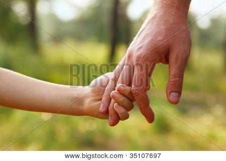 vaders hand leiden zijn zoon kind in de zomer bos natuur buiten, vertrouwen familie concept