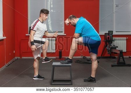 Tired Overweight Man Stands Resting After Doing Hard Exercise In The Gym Under Supervision Of The Pe