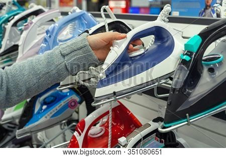 Buyer Chooses An Iron In A Household Appliance Store
