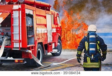 Fireman Wearing Fire Fighter Suit For Safety Under Danger Situation To Fighting With Flame In An Eme