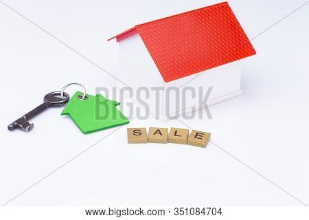 The Photo Shows A White Model House With Wooden Letters And An Old Key