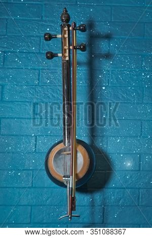 Tar In Front Of Blue Brick Wall .classical Music Concert Poster With Orange Color Tar On Blue Backgr