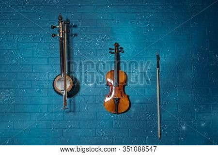Violin In Front Of Blue Brick Wall .classical Music Concert Poster With Orange Color Violin On Blue