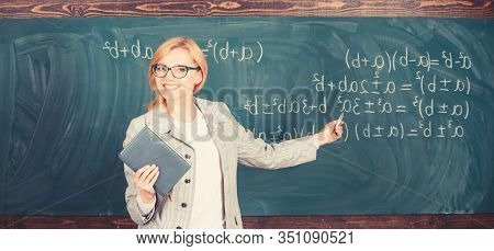 Teacher Smart Woman With Book Explain Topic Near Chalkboard. School Teacher Explain Things Well And
