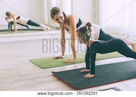 Beautiful sporty woman and little child girl doing together stretching exercise on yoga mat in front of mirror in fitness class
