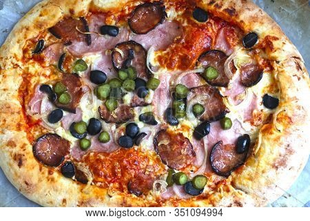 Big Round Hot Pizza With Hum, Sausage,cucumber, Olives Onion And Cheese Close Up Photo