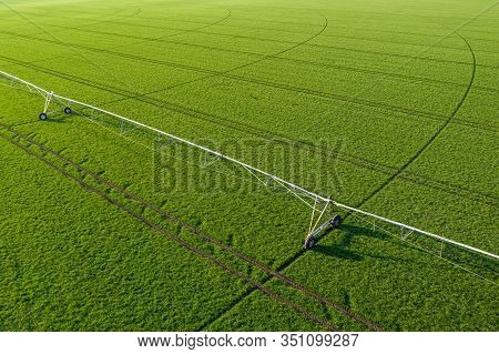 Aerial View Of Center-pivot Irrigation Sprinkler In Young Green Wheat Field, Drone Photography