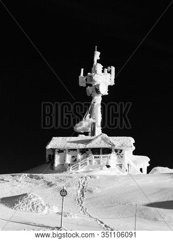Frozen Mountaintop Outpost With Communications Tower At Night.