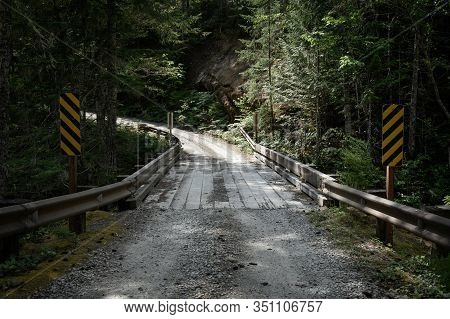 Rickety Wooden Bridge On Dirt Road Leading To Trailhead