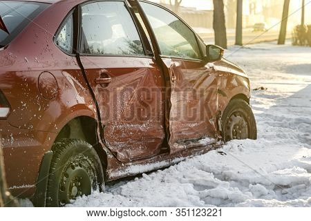 The Broken And Dented Side Of A Red Passenger Car. Winter Accident On A Slippery Road, The Car Flew