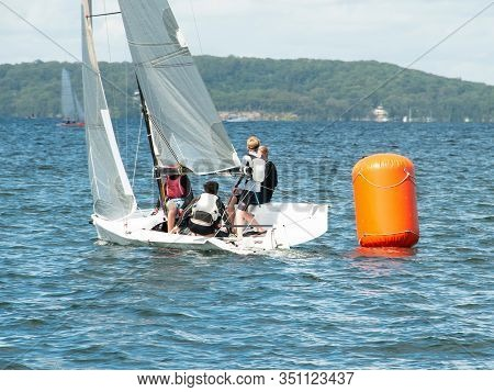 Young Boys Sailing / Racing Small Sailboat, Rounding An Orange Marker. Teamwork By Junior Sailors Ra