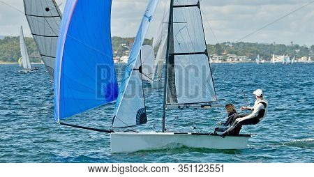 Children Sailing / Racing Small Sailboat With A Blue Spinaker On A Coastal Lake. Teamwork By Junior