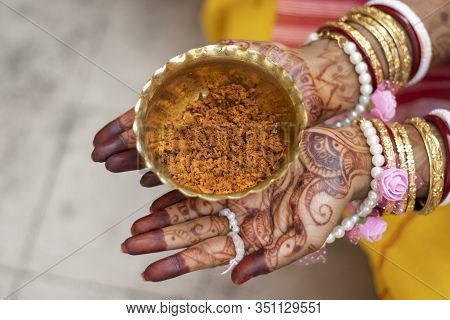 Indian Bride Hand Painted With Mehendi Or Myrtle Holding Brass Bowl Of Turmeric Paste