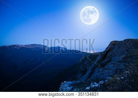 Mesmerizing Picturesque Mountain Landscape With A Full Moon At Night. Concept Of Pristine Nature And