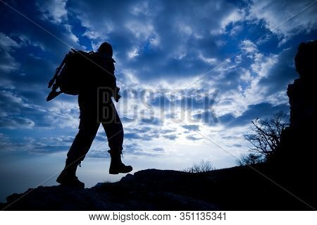 Bottom View Silhouette Of A Male Traveler With A Backpack Climbs Up The Mountains Against A Blue Sky