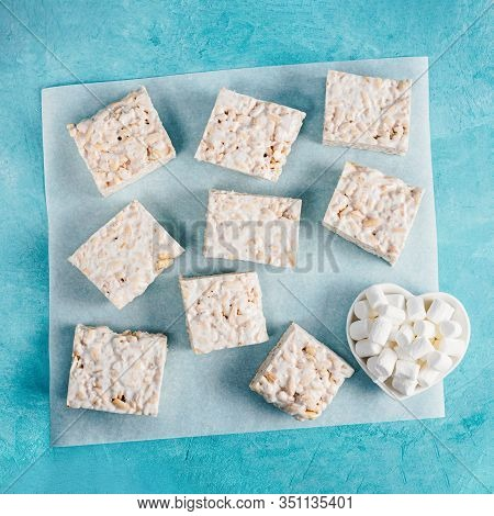 Homemade Square Bars Of Marshmallow And Crispy Rice And Ingredients On Blue Background. American Des