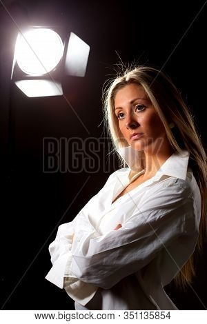 Slender Young Pretty Long-haired Girl Model In A White Shirt Posing In The Studio On A Black Backgro