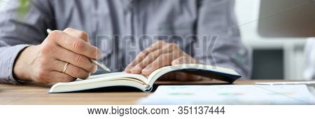 Focus On Male Hands Holding Pen And Writing In Notebook. Job Interview In Office. Employment And Rec