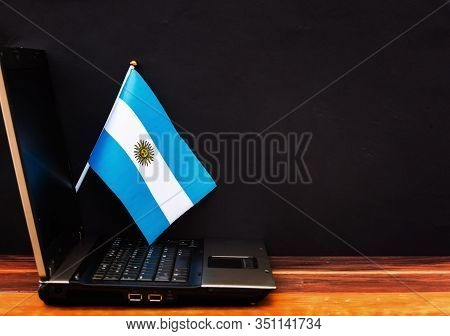 Flag Of Argentina , Computer, Laptop On Table And Dark Background