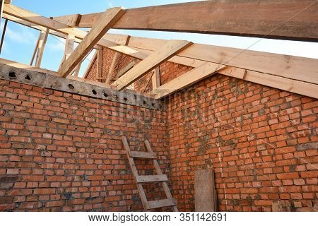 Brick House Attic Rootop Under Construction With Frame Of Wooden Beams, Trusses, Eaves