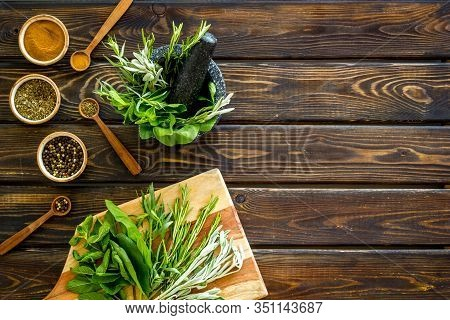 Making . Herbs In Motar And Dry Flavorings On Dark Wooden Desk Top-down Copy Space
