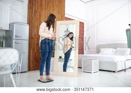Young Woman In A Beige Blouse Standing On A Weigher And Looking At The Mirror