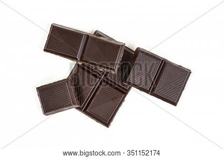 Dark chocolate pieces isolated on white background, with clipping path, flat lay. Carefully retouched.