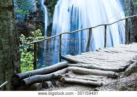 Picturesque Landscape Of A Waterfall In A Forest In The Highlands Next To A Bridge Made Of Wood. Con