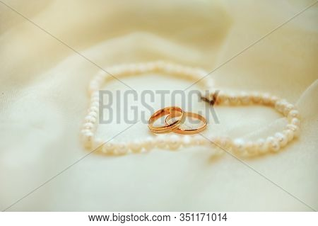 Wedding Rings On Conceptual Creamy Background With Pearl Beads In Forme Of Heart Around. Bride And G