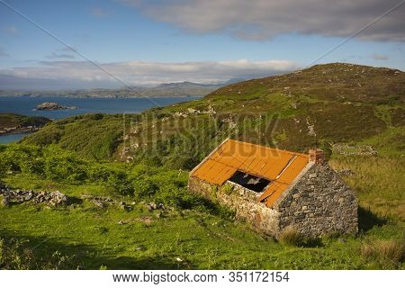 A Traditional Scottish Highlands Blackhouse With A Orange, Tin Roof, Which Is Located In Drumbeg Vie