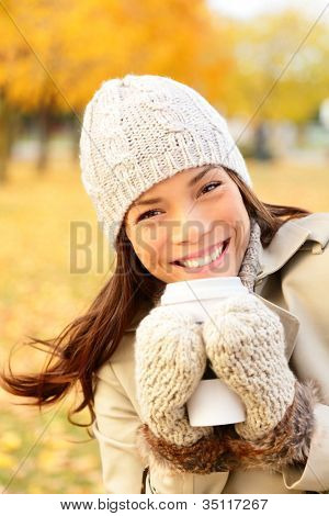 Autumn lifestyle woman drinking coffee. utumn portrait of happy lovely and beautiful mixed race Asian Caucasian young woman in forest in fall colors.