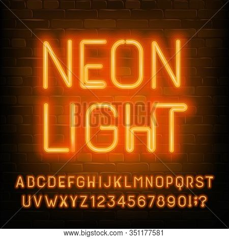 Neon Light Alphabet Font. Orange Neon Light Letters, Numbers And Symbols. Brick Wall Background. Sto
