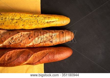 Three Crispy French Baguettes Lie Yellow Cloth Napkin Black Background Baguettes In Assortment With