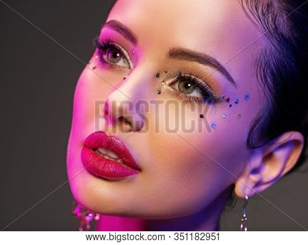 Portrait of the girl is highlighted in bright blue and purple light. Face of a beautiful model. Colorful portrait of a girl with bright makeup. Shiny sequins on the face. Art portrait. Sexy woman.