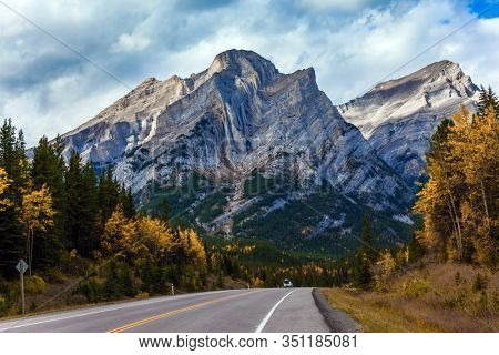 Rocky Mountain asphalt highway. The valley of Kananaskis mountain park. Lush autumn in the Canadian Rockies. The concept of active, ecological and photo tourism