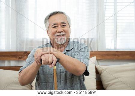 Portrait Of Senior Old Elderly Asian Man Sit On Coach Hand Hold Help Walking Stick Sit On Sofa In Ho